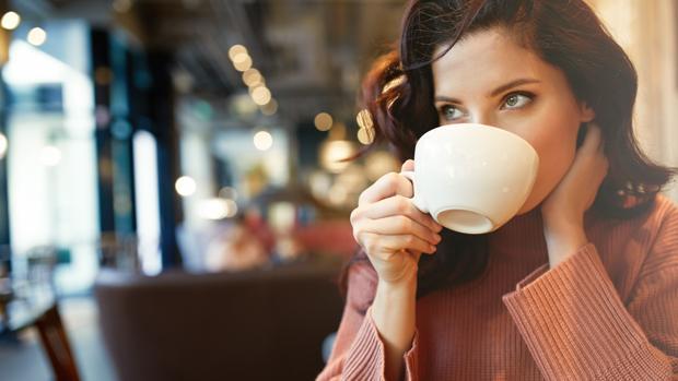 Una joven bebe una taza de café
