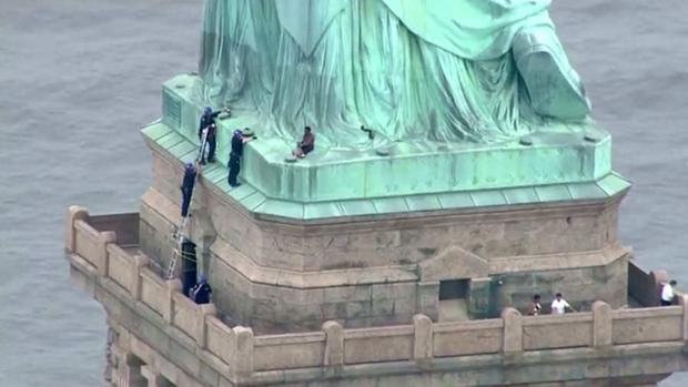 Se observa a la mujer que escala la estatua de la libertad
