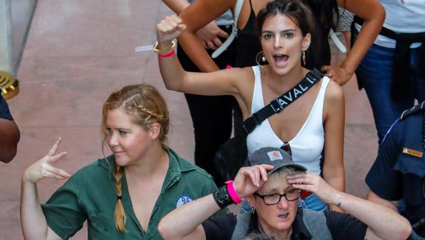 La actriz Amy Schumer y la modelo Emily Ratajkowski realizan un gesto tras ser detenidas junto a 302 mujeres