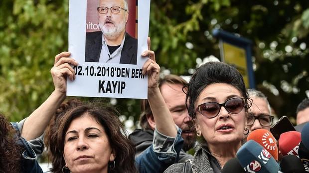 Una mujer sostiene una pancarta con el rostro del periodista asesinado