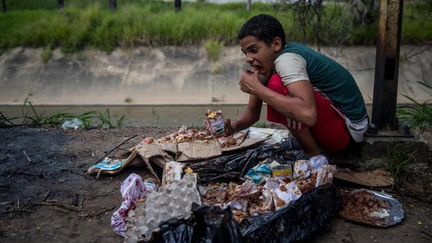 Un niño come de los restos de la basura en Caracas