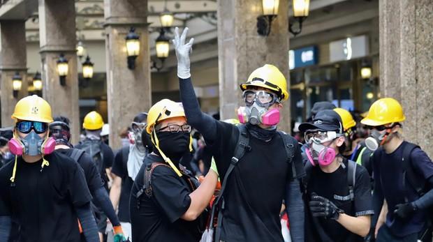 En primera línea de las barricadas, unas jóvenes insultan a la Policía antidisturbios