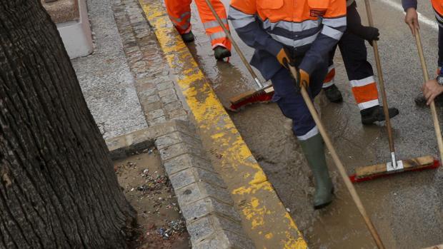 Varios operarios limpian la zona de los bordillos en Cádiz
