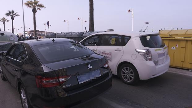 Un coche de Uber junto a un taxi en el Paseo Marítimo.