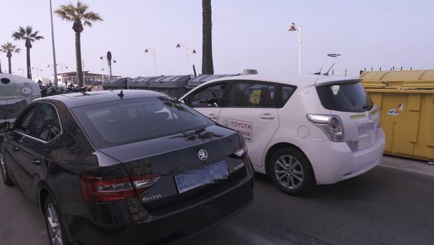 Un taxi circula junto a un Uber estacionado en el Paseo Marítimo en el estreno de la compañía en Cádiz.