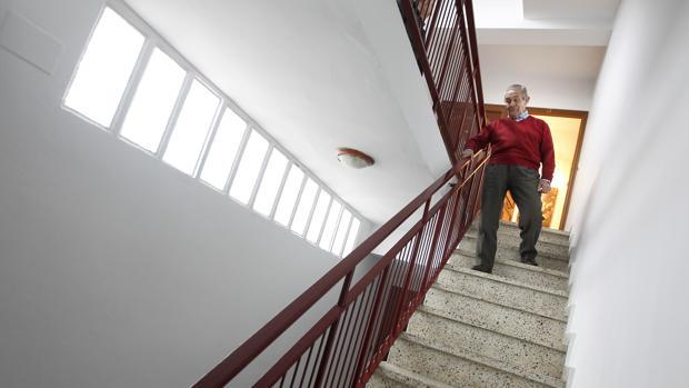 Un anciano baja las escaleras de su bloque que carece de ascensor