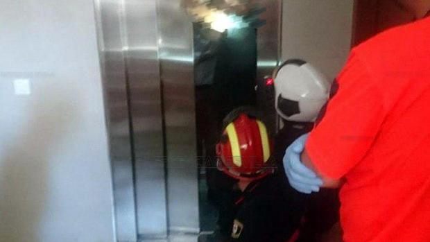 Los bomberos, en el momento en el que rescatan a la persona que cayó con el ascensor