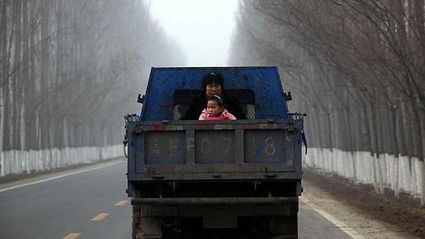 Una mujer, junto a su hija en la parte trasera de una furgoneta en Pekín
